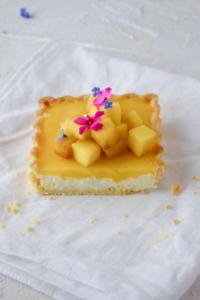 Einfaches Rezept für leckere, süße Mango Milchreis Tartelettes mit Zitronen-Mürbeteig, cremiger Milchreisfüllung und Mangocreme. Dekoriert mit frischen Blüten. Perfekte Obst Tartelettes für den Sommer!