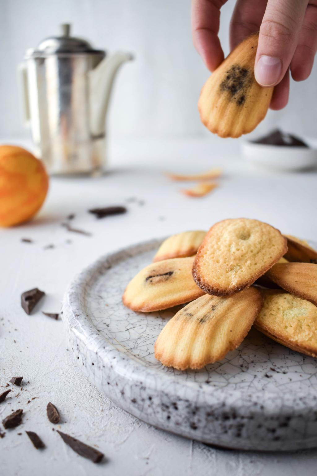Rezept für saftige und schnell gemachte Madeleines mit Orange und einem cremigen Kern aus dunkler Schokolade. Traditionelles französisches Teegebäck.