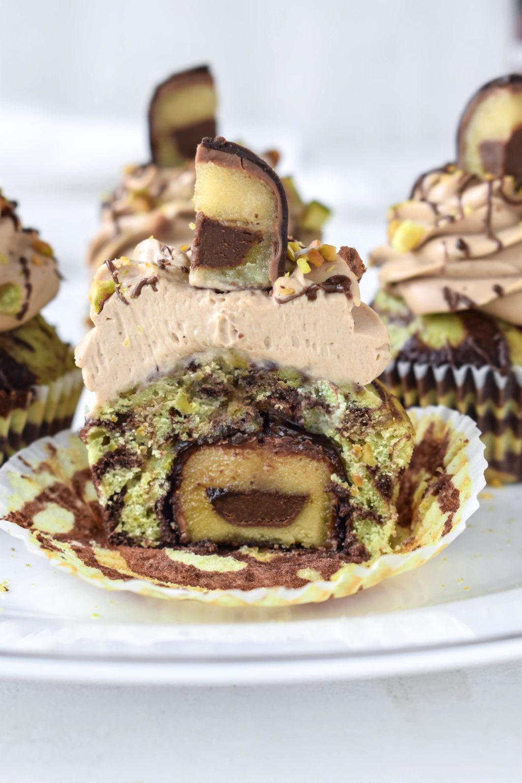 Rezept für Mozartkugel Cupcakes. Pistazien-Schoko Marmor Muffin mit Mozartkugel-Füllung und sahnigem Nougat-Mascarpone Topping.