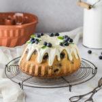 Einfaches Rezept für saftigen Blaubeer Gugelhupf mit Zitrone, Joghurt und Cheesecake Füllung. Leckeres saisonales Kuchenrezept. Zitronenkuchen mit Blaubeeren und Käsekuchen Füllung. #Käsekuchen #Gugelhupf #Saisonal #Cheesecake #Zitronenkuchen #Blaubeer #Blaubeeren